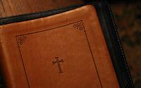 Foto da capa de uma bíblia de couro com uma cruz estampada