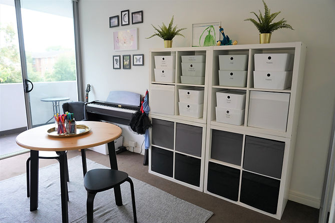 "alt=""white kallax shelf with donas boxes and kuggis containers, ikea gamlared dining table and black stools, electric black piano, guitar, white wall room"""