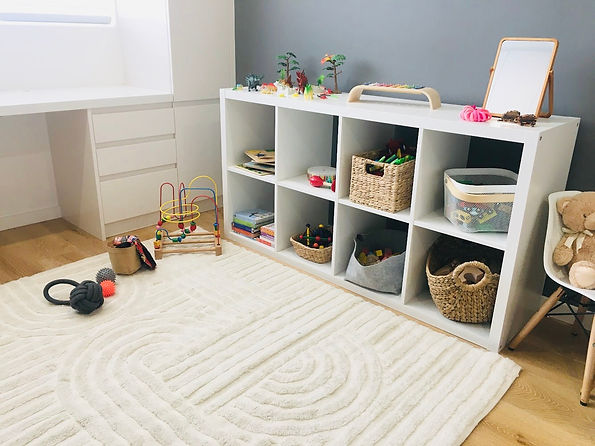 "alt=""white Kmart woolen rig, abacus, ikea kallax white shelf, baskets with toys, wooden toys, wooden blocks, wooden train tracks, books, white shelf and cupboard, charcoal wall"""