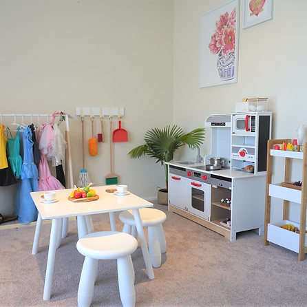 "alt=""play kitchen, dress up clothes on Kmart nursery rack, children'a table and Ikea white stools, palm plant in the corner of the room, white walls"""