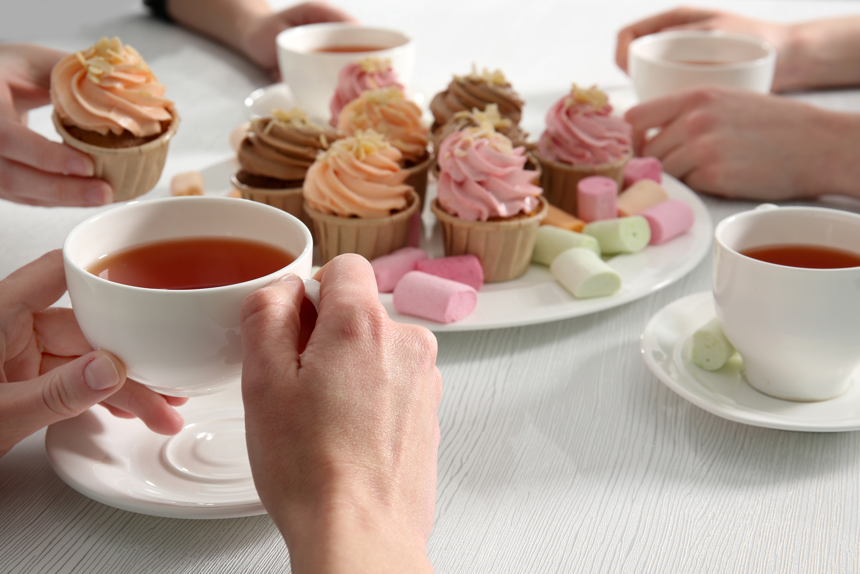 Tea Party with sweet creamy cakes over wooden table background
