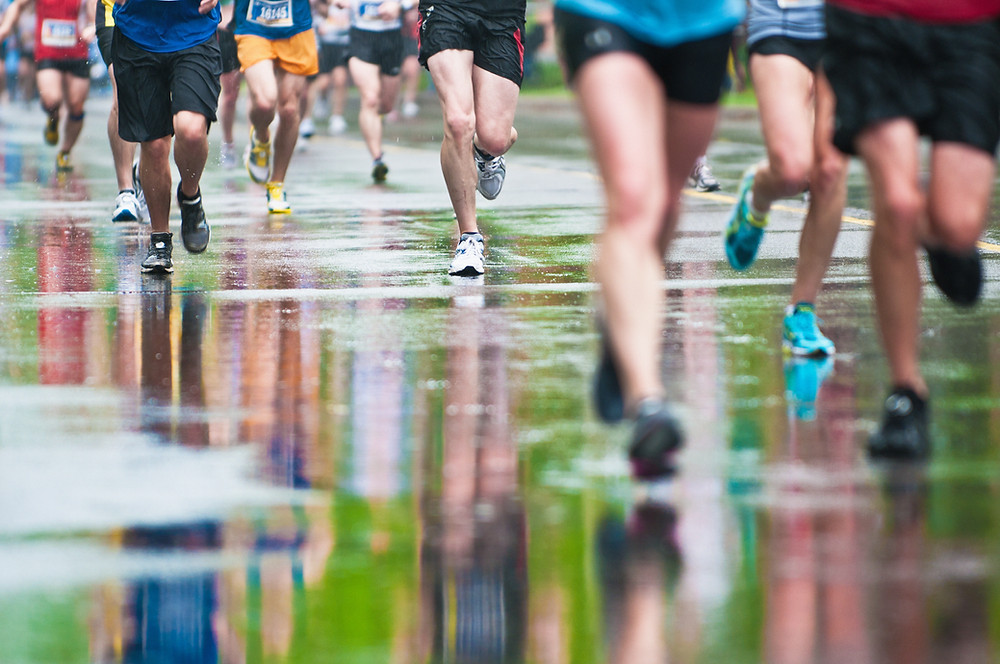 photo of the legs of runners in a race the ground is wet and you can see the reflections