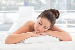 lady laying face down on a towel relaxing after a massage