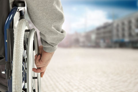 The wheel of a wheelchair is shown, along with a hand pushing the wheel. The background, a city or a town, is blurred.