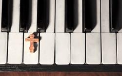 Wooden cross on piano keys, top view