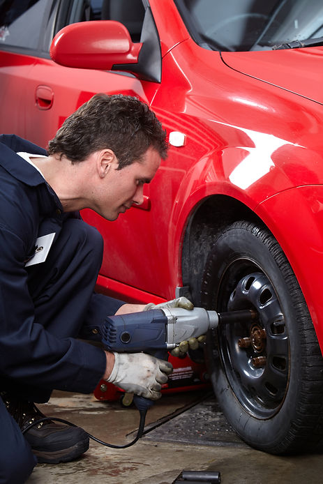 Mechanic changing wheel on car with impa