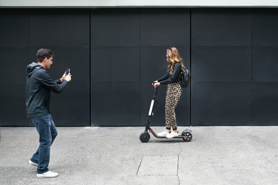 Man taking picture of lady on electric scooter
