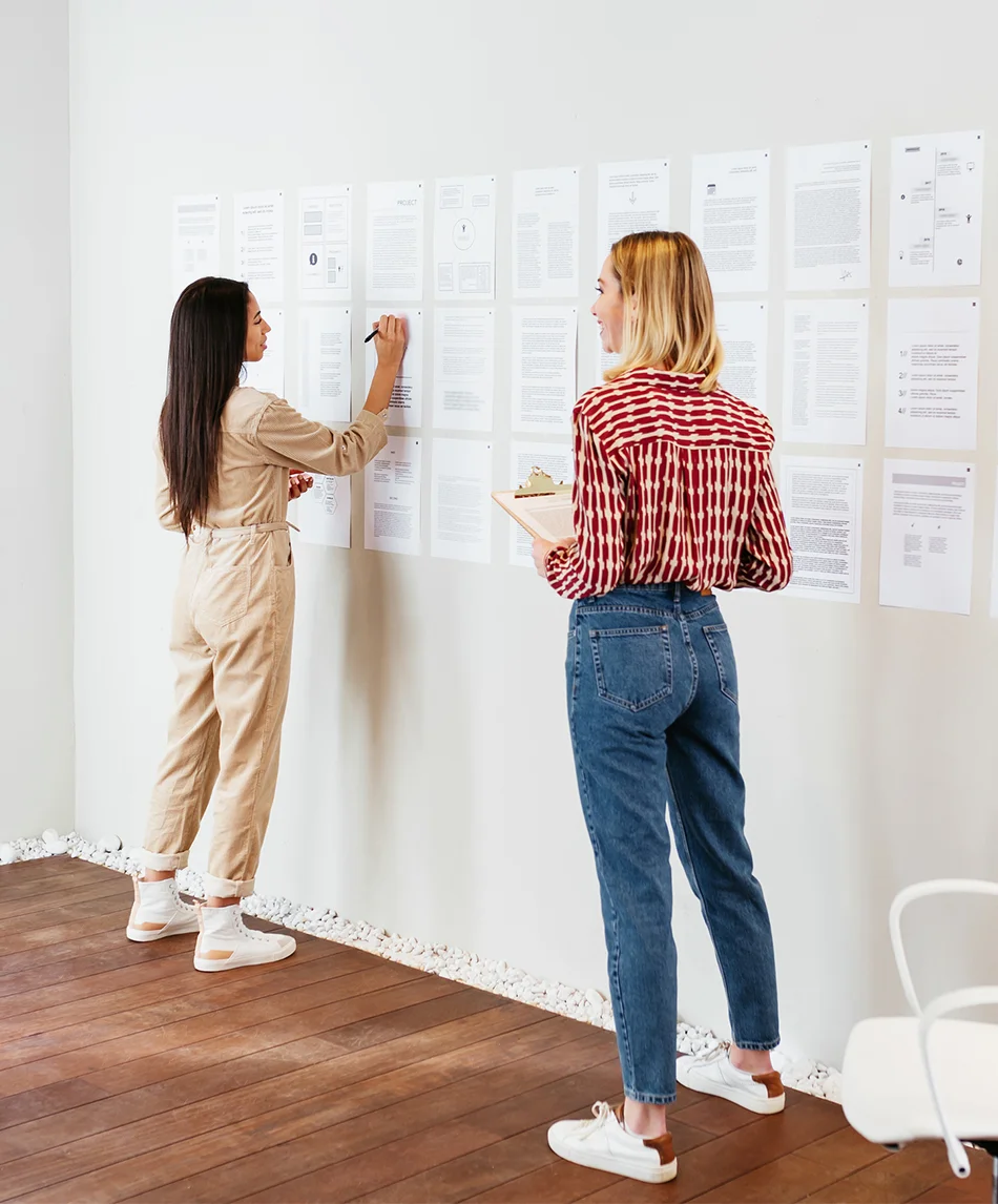 Two women writing notes on the wall