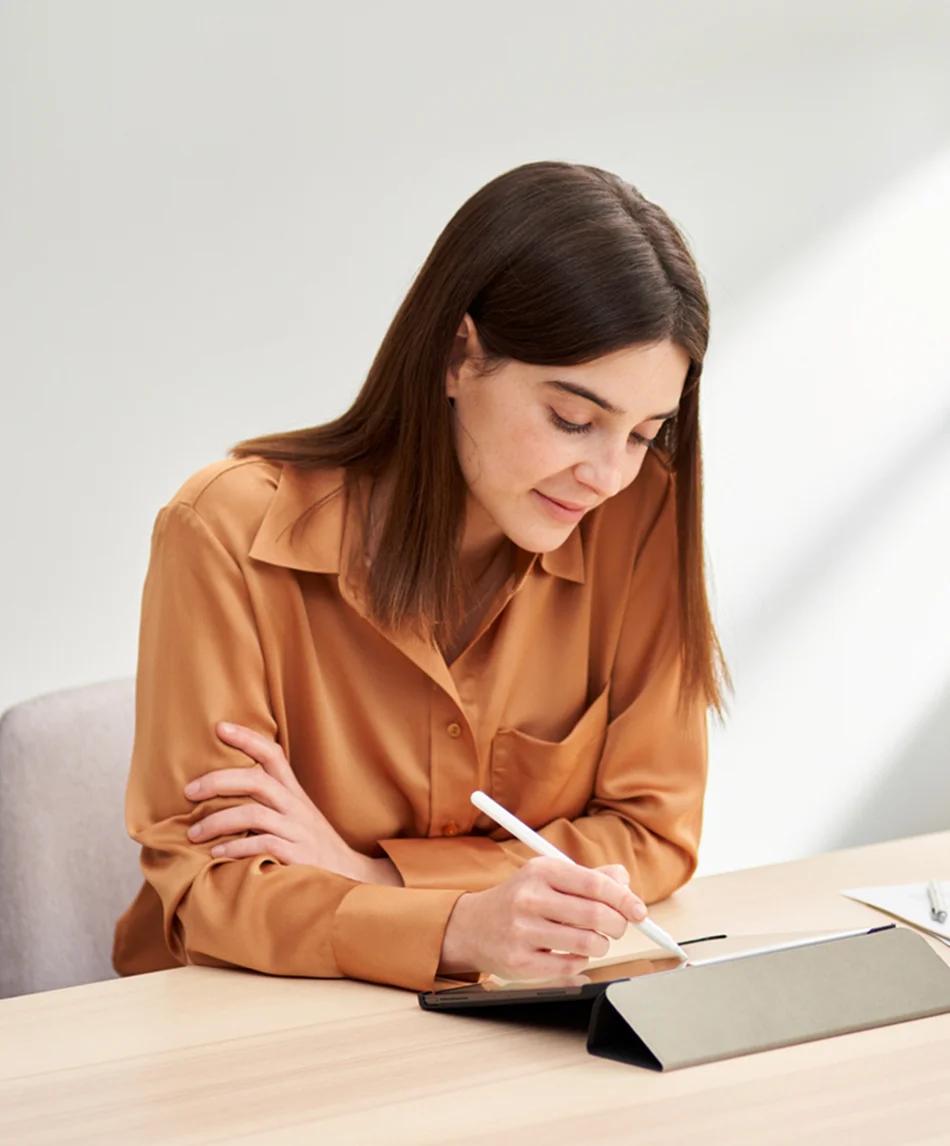 Woman with orange shirt drawing on iPad