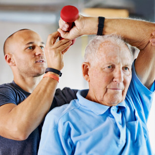 Older senior citizen male exercising with a personal trainer