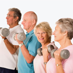 Smiling senior woman exercising in group fitness class