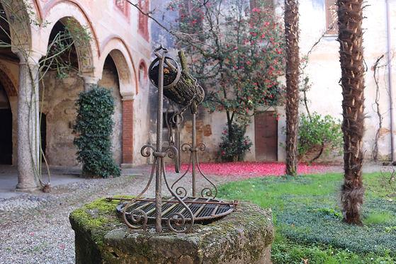 Suggestivo angolo del giardino di Casa Pisani Dossi con l'antico pozzo e la secolare camelia