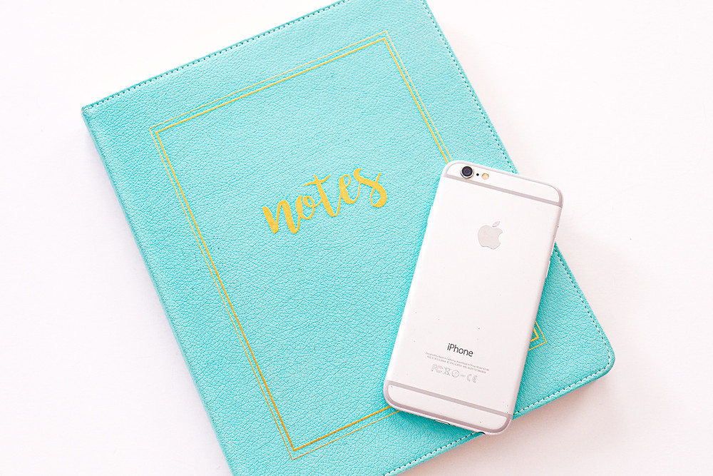 iPhone on teal notebook