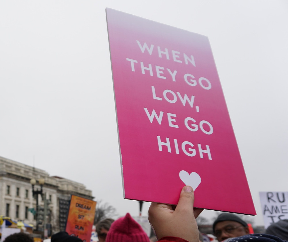 Protesters hold up when they go low we go high signs