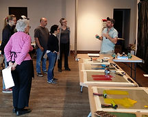 Group listens as artist explains workshop.