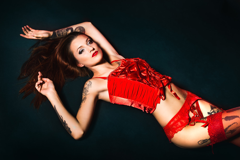Girl lays on black backdrop in red lingerie