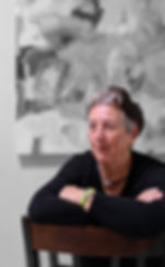 Artist Rene Griffith sitting in front of her painting Wine and Roses.