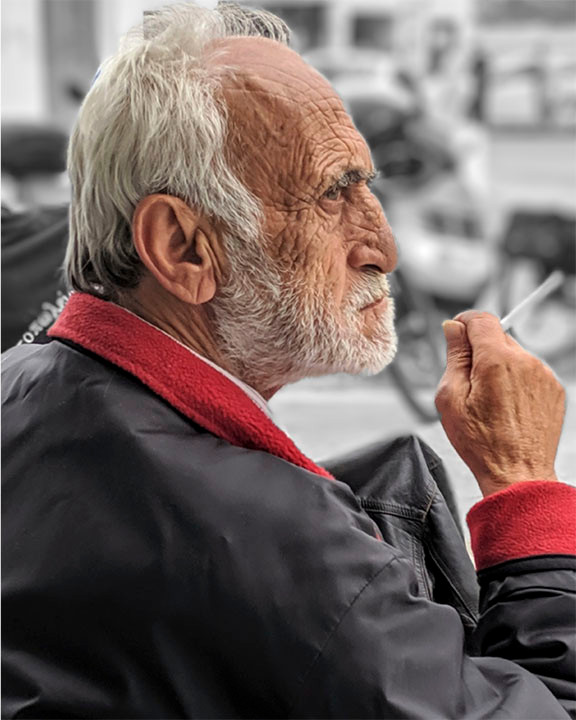 Man with a face full of character and the signs of a life fully lived waiting for a ferry on a Greek island.