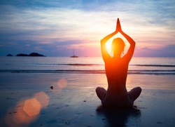 Silhouette young woman practicing yoga on the beach at sunset.jpg