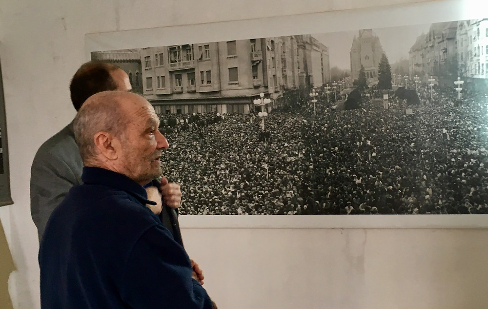 Dr Orban, wounded hero of 1989 Revolution, in front of photo; composer Aaron Garber in background