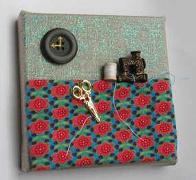 """""""L'atelier de la couturière""""  Tableau en toile de lin sur châssis, 10 x 10 cm, boutons, tissu, paillettes. Les fils, mobiles, peuvent être positionnés différemment."""