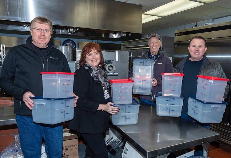 Colin Park and Megan Schain of Cohen & Park and Keith Nelson and Freddy Saxton representing the Rotary Club of Newport show off donated food bins.