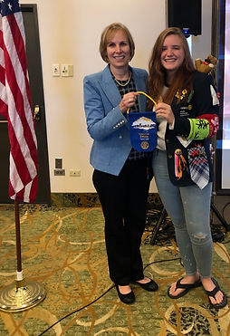 Outbound exchange studentRilee Anderson hands Pres. Hanrahan a Rotary flag from her travels.