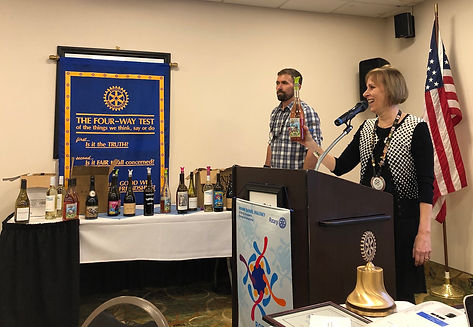 Rotary of Newport, Oregon President Hanrahan and Rob Wienert selling some of the extra wine from the Newport Seafood & Wine Festival.