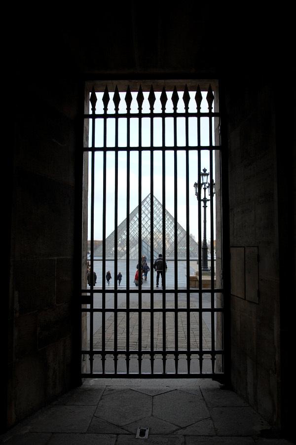 louvre pyramid behind bars