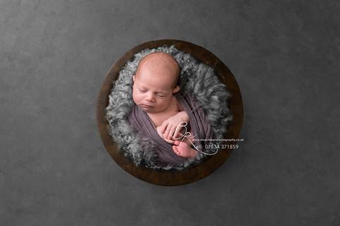 newborn-baby-boy-wrapped-in-bowl-blue-ri