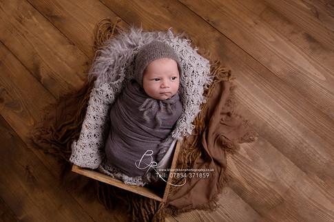 newborn-baby-boy-wrapped-in-prop-blue-ri