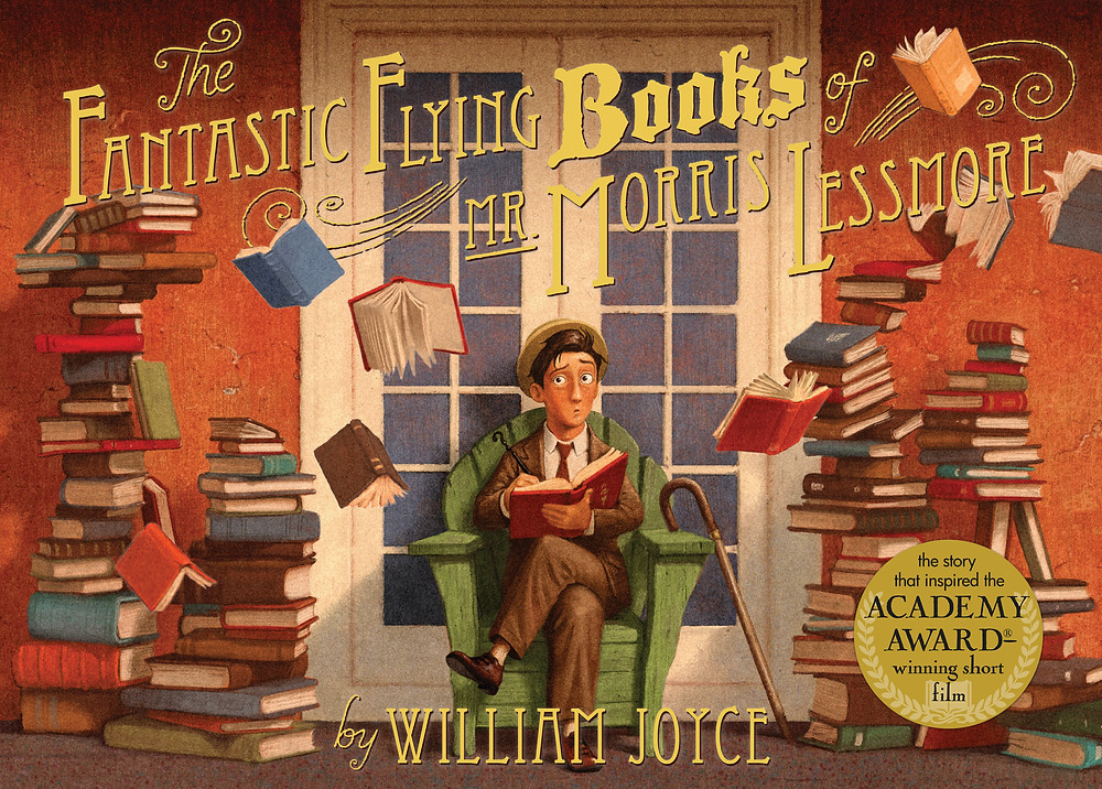 The cover of The Fantastic Flying Books of Mr. Morris Lessmore featuring a man in a brown suit sitting in a chair in front of a door with stacks of books on either side of him.