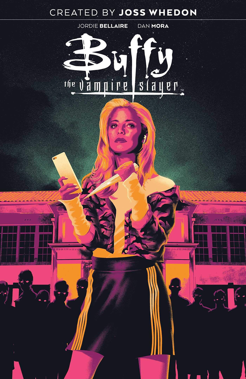 On the cover of issue one of Buffy the Vampire Slayer, a girl stands in front of a school wearing a skirt and sweater. She holds a stake in one hand and a cell phone in another. Behind her is a shadowy crowd of figures with glowing eyes.
