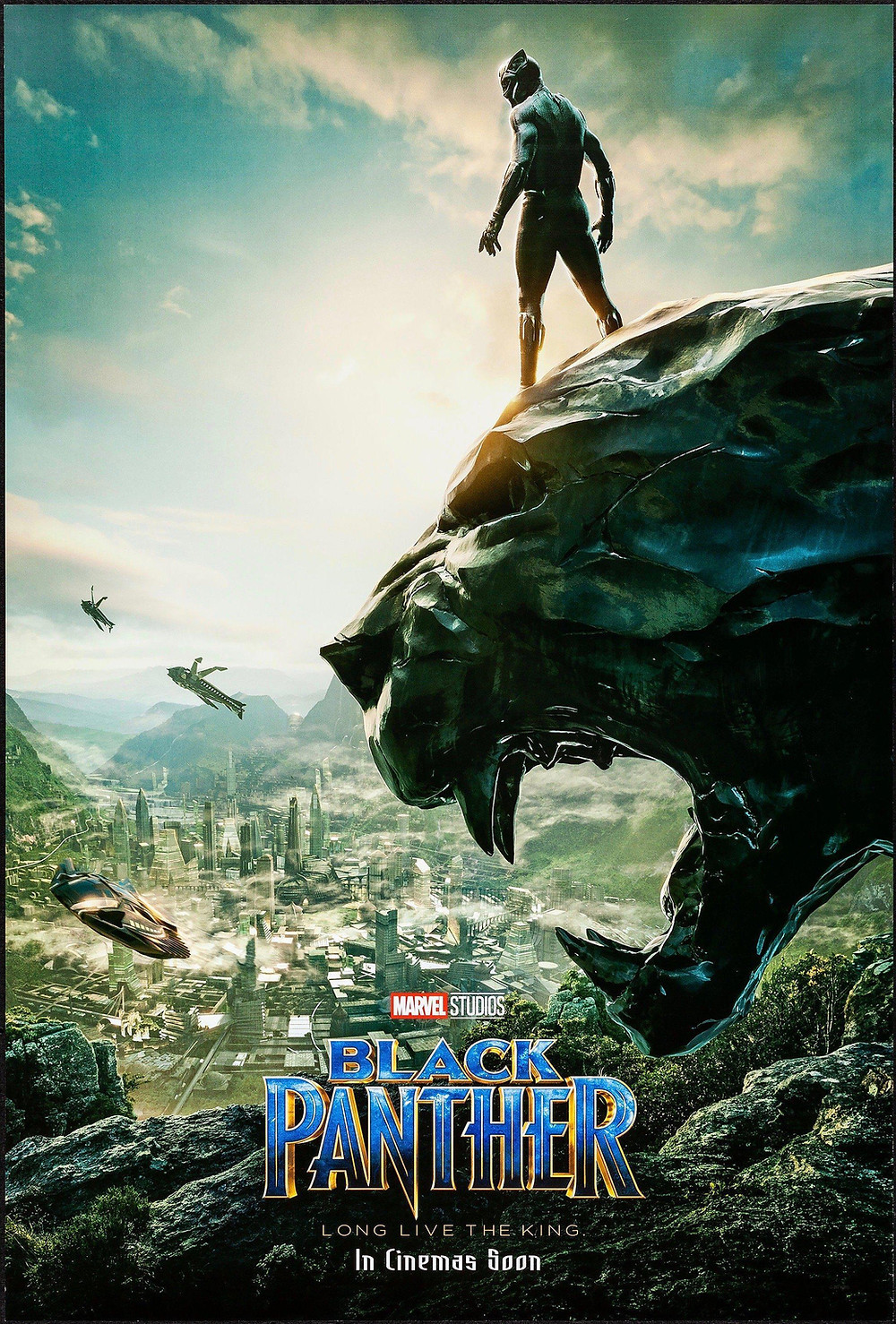 The Black Panther superhero stands on the head of a large panther statue looking out over the Kingdom of Wakanda. A technologically advanced city is in the valley below him.