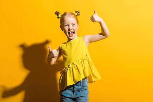 Ein kleines glückliches Mädchen, welches mit den Daumen nach oben zeigt.