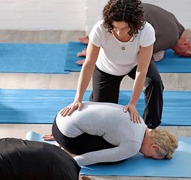 Yoga teacher adjusting in Childs pose Cr