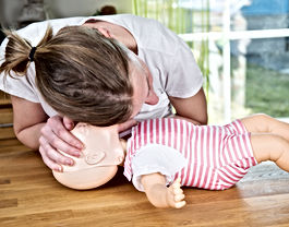 Woman performing CPR on baby training do