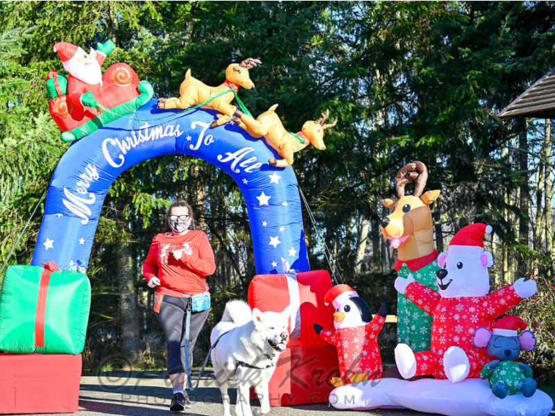 A woman and her dog pass under the arch at the 2020 ATFS Ugly Sweater Run
