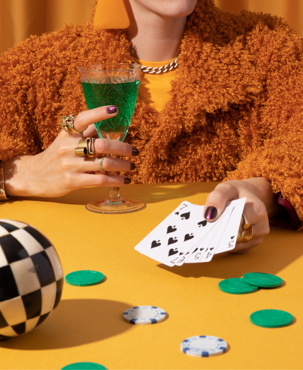 Women holding a cocktail and playing card