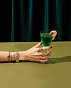 Women hand adorned with jewelry holding a cocktail