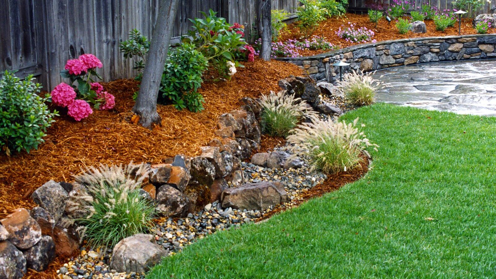 fieldstone-wall-connects-a-patio-landsca