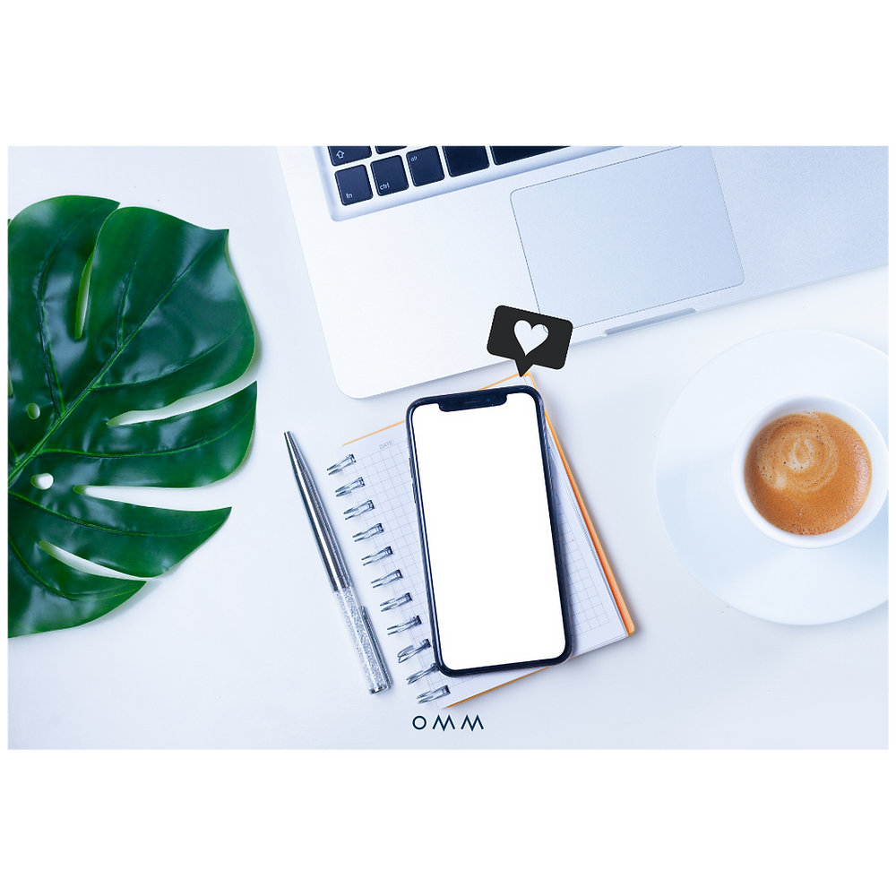 An image of a leaf from a plant, a cappuccino, they keyboard of an Apple Macbook, and a spiral notebook sitting open with an iPhone sitting atop of it with a 'heart' like icon that appears above the iPhone.