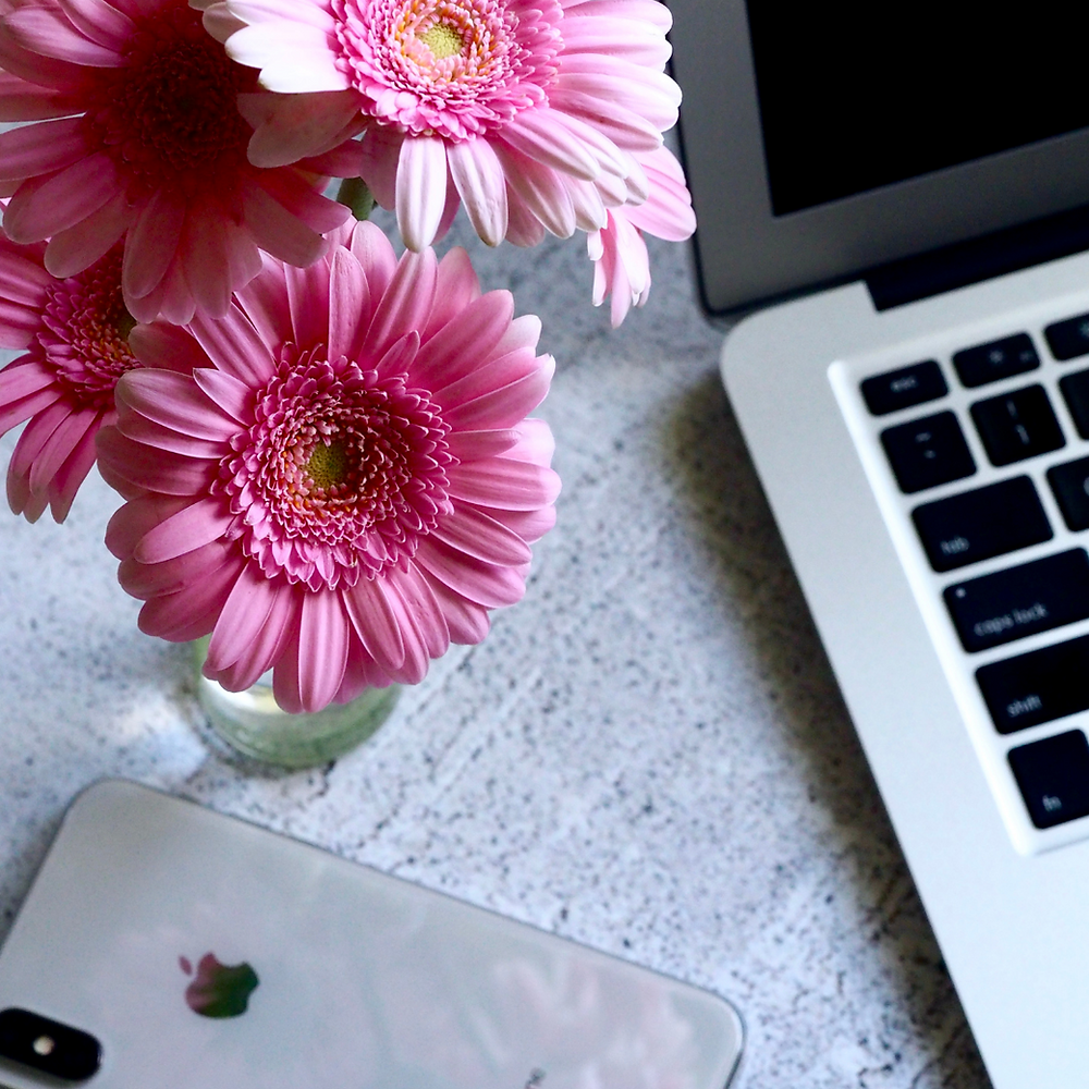 An image of a Macbook laptop and an iPhone placed next to one another, with a small bouquet of pink sunflowers sitting in-between the two.