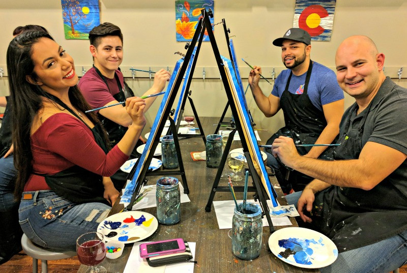 Date night couple and their family sipping and painting