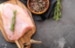 Raw turkey fillets on black cutting boar
