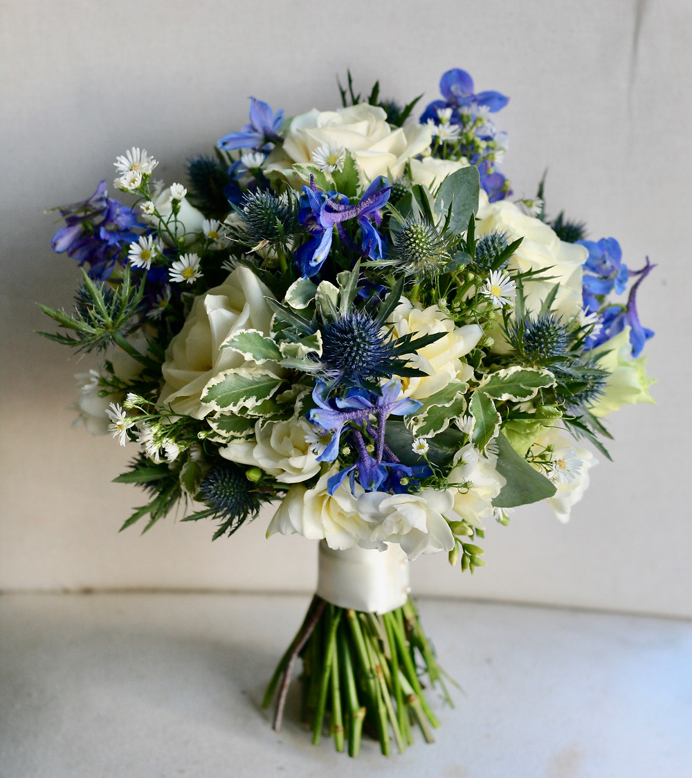Bridal bouquet of delphiniums, roses and thistles