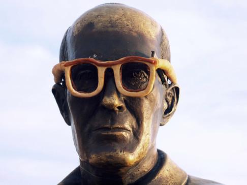 Stuffed cookie glasses, 2015.   Óculos de biscoito recheado, 2015.  Intervention - Carlos Drummond Andrade statue, Copacabana, RJ.   Intervenção - estátua de Carlos Drummond de Andrade, praia de Copacabana.