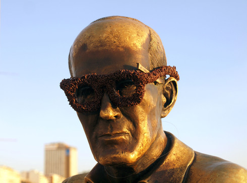 """""""Chocolate truffle"""" glasses, 2015.  Óculos de brigadeiro, 2015. Intervention - Carlos Drummond Andrade statue, Copacabana, RJ.   Intervenção - estátua de Carlos Drummond de Andrade, praia de Copacabana."""