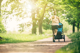 Running woman with baby stroller enjoyin