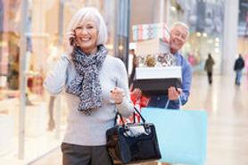 senior-woman-shopping-mall-as-husband-ca